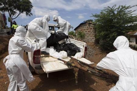 Burial team remove body of suspected Ebola virus victim in Freetown