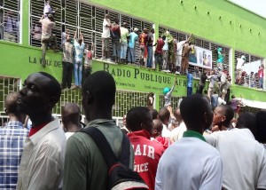 """Burundians throng outside the headquarters of the popular private radio Radio Publique Africaine (RPA) - nicknamed """"Radio of the voiceless"""" for a second day, on February 19, 2015  in Bujumbura, to express their joy at the release on bail of its director Bob Rugurika. The streets of the Burundian capital Bujumbura were covered with people several kilometers, today to host popular journalist and critic of the government  just released from prison, a signal sent to President Pierre Nkurunziza at the approach of key elections .. AFP PHOTO/Esdras NDIKUMANA"""
